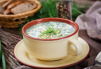 Summer yogurt cold soup with egg, cucumber, and dill on wooden table. Okroshka. Russian food